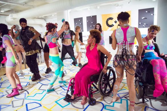 Photo by Kiam Marcelo Junio. A group of people wearing colorful, geometric Rebirth Garments dance during one of their performances. In the foreground, a dancer in a wheelchair is wearing a long, hot pink dress. The floor is painted with blue and yellow squares and shapes.