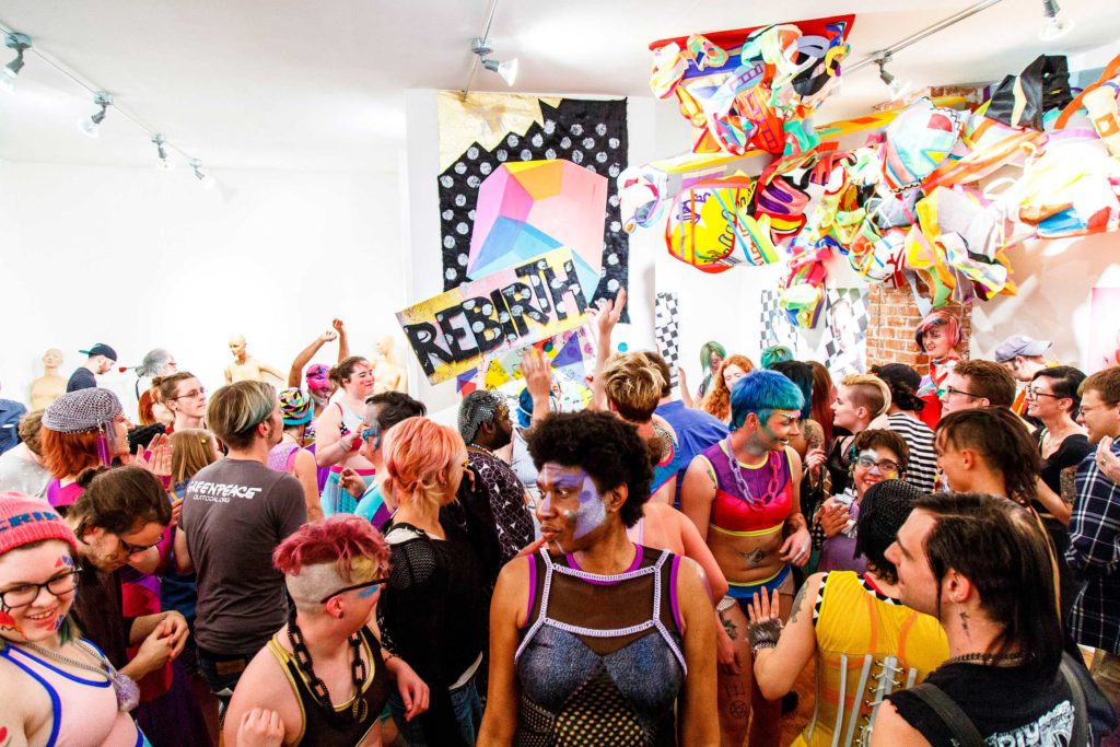 Photo by Grace Duval. A crowd of people with blue, pink, red, green, and brown hair and wearing bright spandex clothing by Rebirth Garments fill a room with rainbow abstract art hanging from the ceiling. In the back of the room, a large sign says